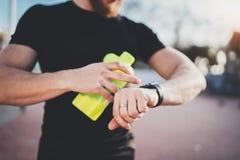 Muskulöser junger Athlet, der Herzfrequenz und gebrannte Kalorien auf seiner Smartphoneanwendung nach dem guten Training im Freie Stockfotos