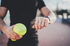Muskulöser junger Athlet, der Herzfrequenz und Kalorien auf seiner Smartphoneanwendung nach Sitzung des guten Trainings im Freien Lizenzfreies Stockbild