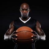 Muskulöser junger Basketball-Spieler mit einem Ball Lizenzfreies Stockbild