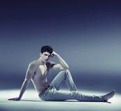 Muskulöser junger Kerl in der sexy Haltung lizenzfreie stockbilder