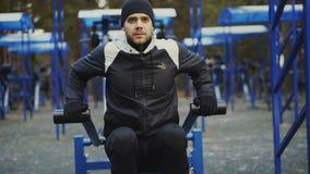 Muskulöser junger Mann, der Übung Turnhalle in der im Freien im Winterpark tut stock footage