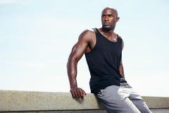 Muskulöser junger Mann, der copyspace draußen weg betrachten sitzt Stockbilder