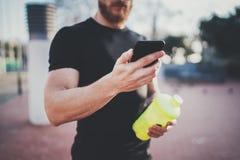 Muskulöser junger Mann, der gebrannte Kalorien auf Smartphoneanwendung nach Sitzung des guten Trainings im Freien auf sonnigem Pa Stockfotografie