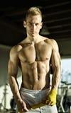 Muskulöser junger Mann, der Verband um seine Hände einwickelt Stockbilder