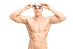 Muskulöser junger Schwimmer mit einer grauen Schwimmenkappe Stockbild