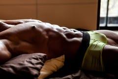 Muskulöser junger sexy Mann liegt auf dem Bett Stockfotografie