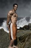Muskulöser Kerl durch den Ozean Stockfotografie