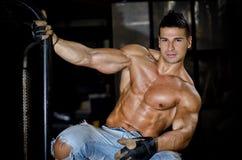 Muskulöser Latinobodybuilder in den Jeans, die vom Metallgriff hängen Lizenzfreie Stockfotos