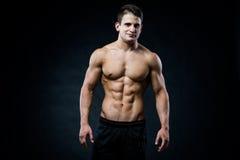 Muskulöser männlicher vorbildlicher Bodybuilder, der gerade zur Kamera schaut auf Schwarzem Stockbild