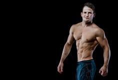 Muskulöser männlicher vorbildlicher Bodybuilder, der gerade zur Kamera schaut Lokalisiert auf Schwarzem Lizenzfreie Stockfotos
