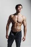 Muskulöser männlicher vorbildlicher Bodybuilder mit aufgeknöpften Jeans Studio SH Stockbilder