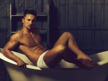 Muskulöser Mann auf Badewanne lizenzfreies stockbild