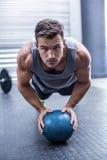 Muskulöser Mann auf einer Plankenposition mit einem Ball Lizenzfreie Stockfotografie