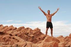 Muskulöser Mann auf roten Felsen Lizenzfreies Stockfoto