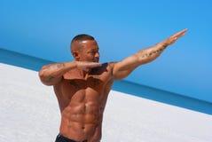 Muskulöser Mann auf Strand in einer positiven Haltung Lizenzfreie Stockfotografie