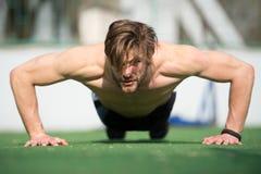 Muskulöser Mann, den das Handeln drückt, ups, männlicher Athlet das Trainieren hochdrücken Stockbild
