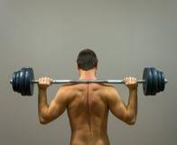Muskulöser Mann, der Übungen mit Barbell tut Stockbild