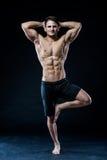 Muskulöser Mann, der auf dem einem glaubenden entspannten dunklen Hintergrund des Beines balanciert Lizenzfreies Stockfoto