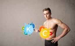 Muskulöser Mann, der bunte Vitamingewichte anhebt Stockfoto