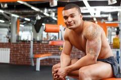 Muskulöser Mann, der in der Hand sitzt und hält Lizenzfreie Stockfotos