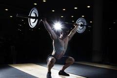 Muskulöser Mann, der die crossfit Übung in der Turnhalle tut stockbild