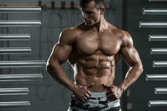 Muskulöser Mann, der die Muskeln, werfend in der Turnhalle zeigt auf Starke männliche nackte Torso-ABS, arbeitend aus stockfoto