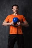 Muskulöser Mann, der ein kettlebell in den Händen hält Lizenzfreies Stockfoto