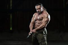 Muskulöser Mann, der Gewehr hält Lizenzfreie Stockfotos