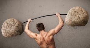 Muskulöser Mann, der große Felsensteingewichte anhebt Stockfotografie