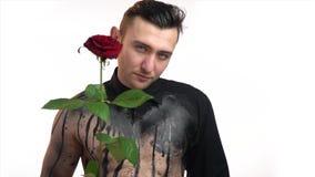 Muskulöser Mann in der Kunst des schwarzen Körpers, gibt eine rote Rose stock video