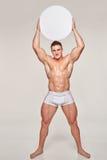 Muskulöser Mann, der leeren Kreiskopienraum emporhebt Stockbild