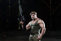 Muskulöser Mann, der Maschinengewehr hält Lizenzfreie Stockfotos