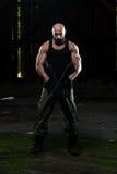 Muskulöser Mann, der Maschinengewehr hält Stockbilder