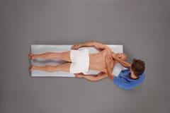Muskulöser Mann, der Massage durch Therapeuten ist Lizenzfreies Stockbild