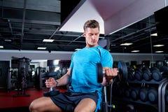 Muskulöser Mann, der mit Dummköpfen in der Turnhalle ausarbeitet lizenzfreies stockfoto