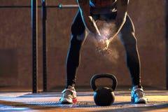 Muskulöser Mann, der mit kettlebell in der Turnhalle trainiert stockfotos