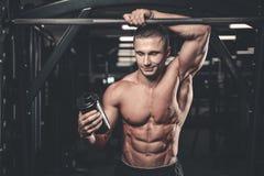 Muskulöser Mann, der nach Übung stillsteht und vom Schüttel-Apparat trinkt stockbilder