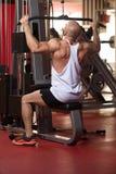 Muskulöser Mann, der Schwergewichts- Übung für Rückseite tut Lizenzfreie Stockfotos