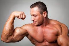 Muskulöser Mann, der seinen zweiköpfigen Muskel biegt Lizenzfreies Stockfoto