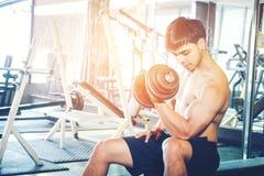 Muskulöser Mann errichtete den Athleten, der in der Turnhalle ausarbeitet, die auf weightl sitzt Lizenzfreie Stockbilder