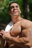 Muskulöser Mann hemdlos in den Jeans draußen unter Bäumen Stockfoto