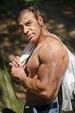 Muskulöser Mann hemdlos in den Jeans draußen unter Bäumen Stockfotografie