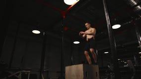 Muskulöser Mann ohne ein Hemd führt vertikale Sprünge auf einer Holzkiste durch Aerobe Übung stock video