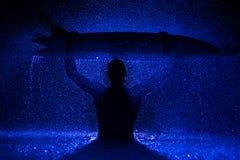 Muskulöser Mann und Surfbrett im Wasser Stockfotografie