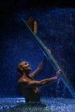 Muskulöser Mann und Surfbrett im Wasser Lizenzfreies Stockfoto