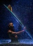 Muskulöser Mann und Surfbrett im Wasser Lizenzfreie Stockfotografie