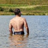 Muskulöser Mann von mittlerem Alter badet im kleinen Vorstadtsee im Sommer R?ckseitige Ansicht stockfotografie