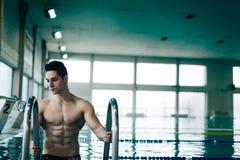 Muskulöser Schwimmer auf der Leiter Stockfoto
