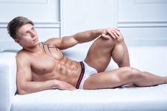 Muskulöser sexy junger Nackter, der auf dem Sofa liegt Stockbild