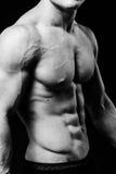 Muskulöser sexy Torso des jungen sportlichen Mannes mit perfekter ABS schließen oben Schwarzweiss auf schwarzem Hintergrund Lizenzfreie Stockfotografie